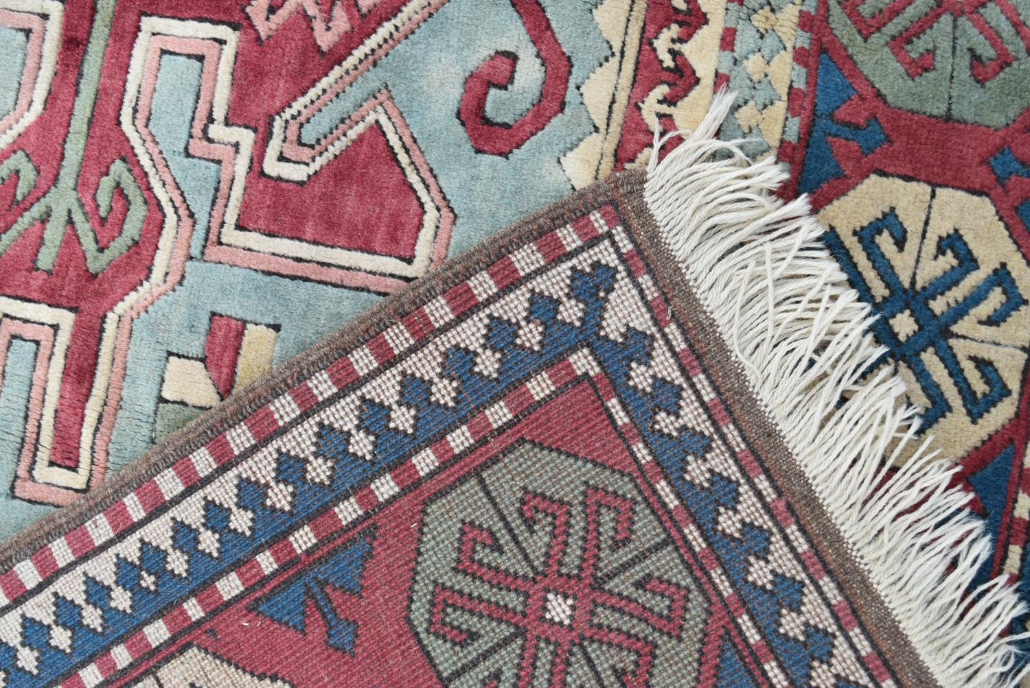 A Turkish Kazak carpet with triple stylised gul medallions on a fawn ground within stylised - Image 4 of 5