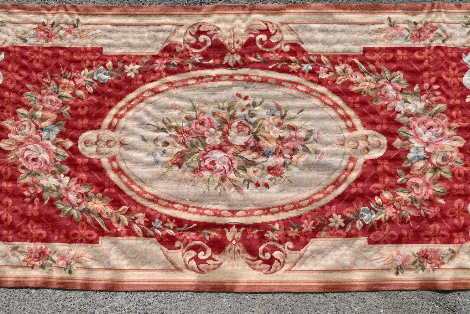 A needlepoint rug with central floral cartouche on a burgundy field within ribbon and flowerhead - Image 2 of 4