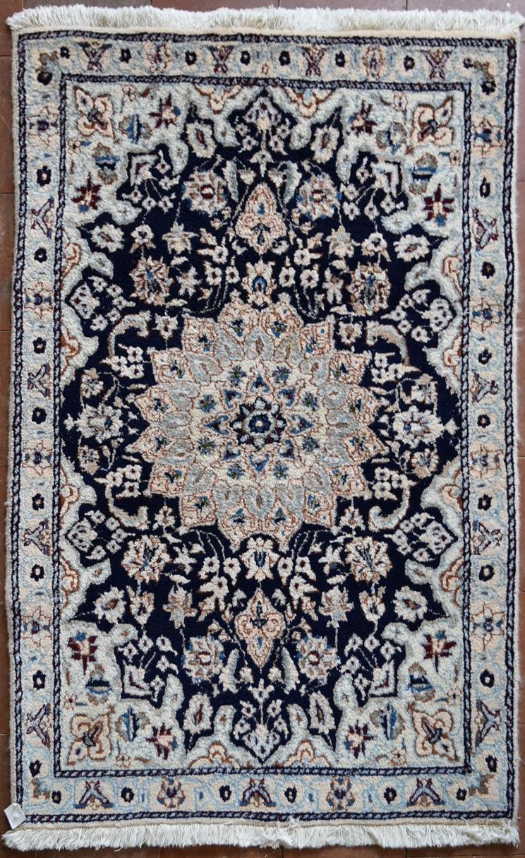 A Persian silk & wool Naiin rug with central floral medallion on a midnight ground within floral