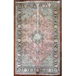 a Kashmir silk rug with floral medallion and spandrels on a salmon ground depicting animals in a