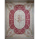 A handmade needlepoint rug with double floral central medallions contained by flower and vine