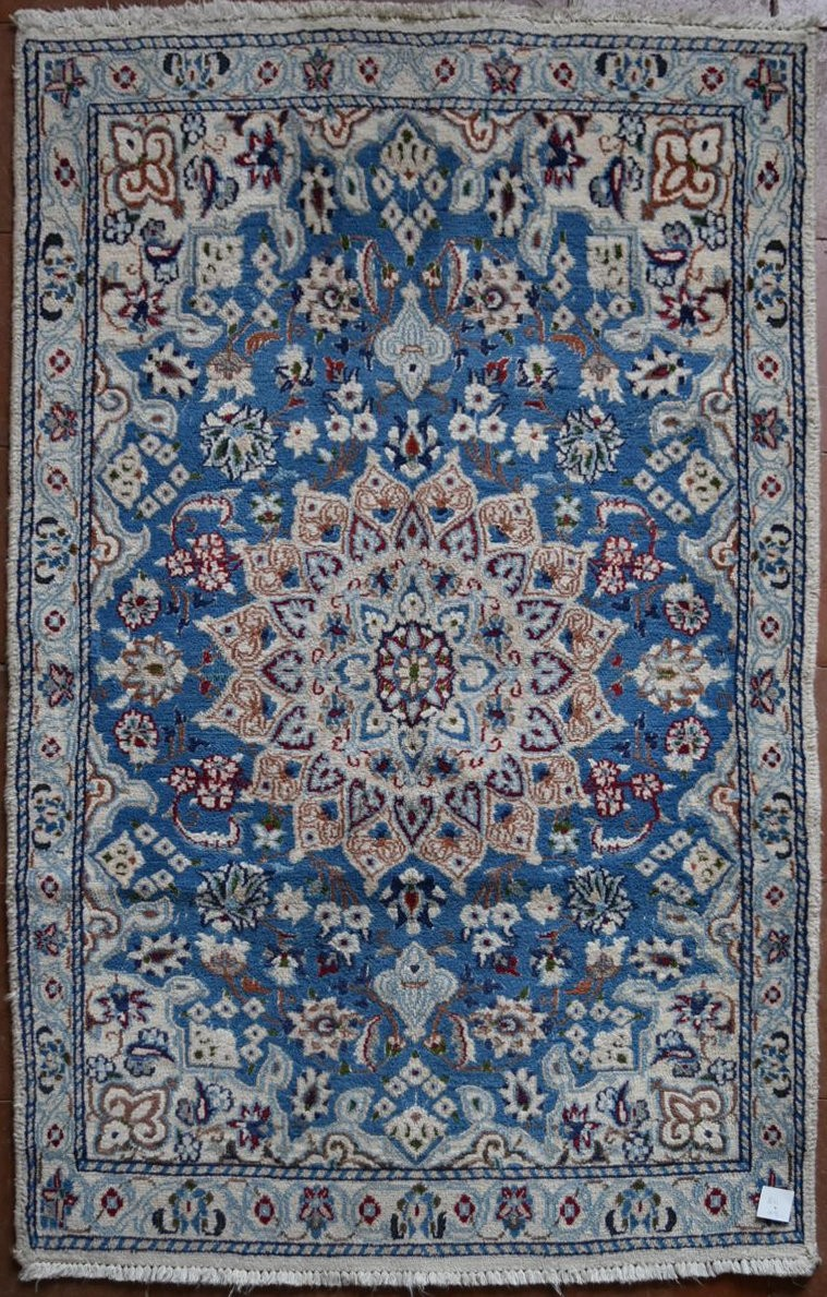 A Persian silk & wool Naiin style rug with central medallion on pale blue ground contained by a