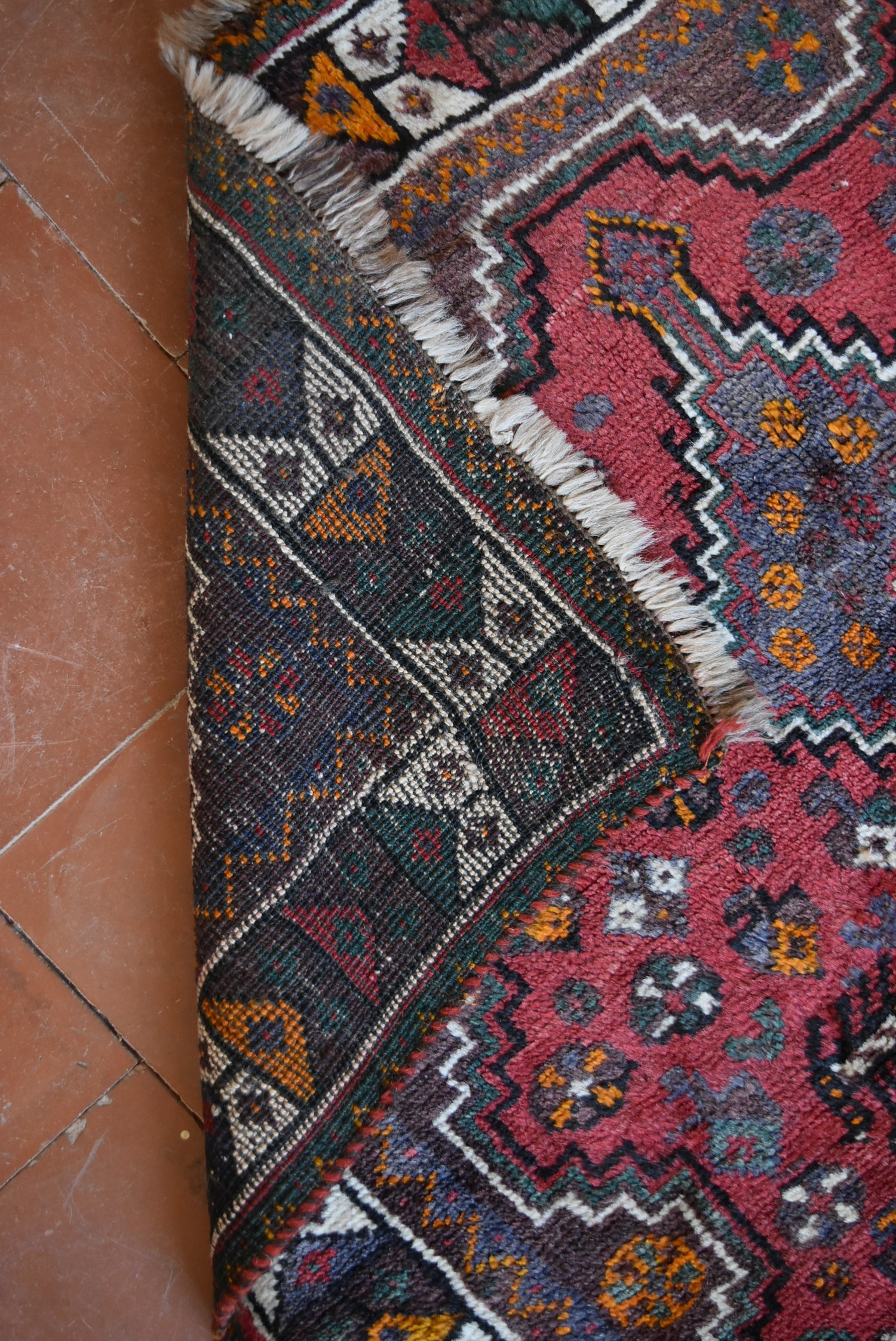A Persian Shiraz rug with triple stepped pole medallion on burgundy field with stylised animal and - Image 4 of 4