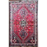 A Persian Shiraz rug with triple pole medallions on a madder ground contained by stylised floral