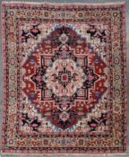 A Heriz carpet with highly stylised central star medallion on a madder field decorated with stylised