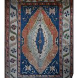 A Turkish Kazak rug with quadruple central medallions on an azure field within stylized triple