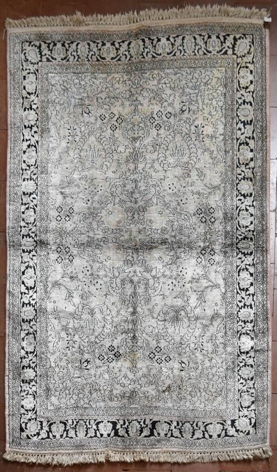 A Kashmir silk rug with all over scrolling floral design contained by foliate multi borders. L.