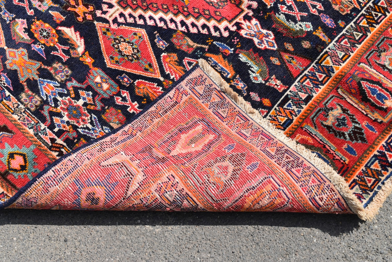 A Persian Kashkai rug with triple hooked medallions on a midnight ground within a stylised multi - Image 4 of 4