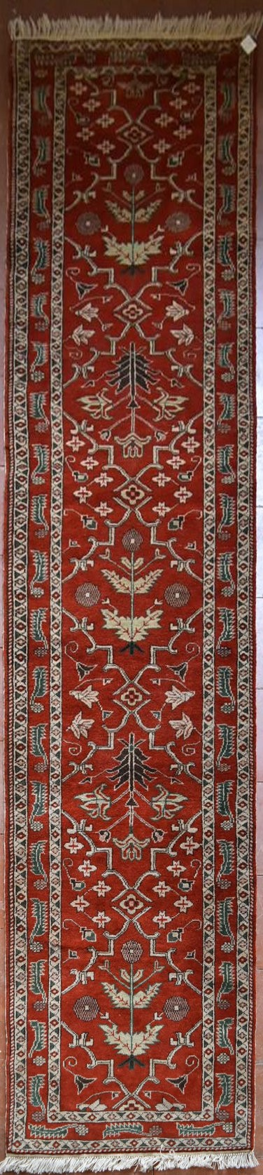 A Moughal style runner with repeating scrolling trellis central design within a border of serrated