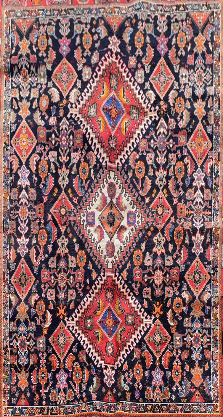 A Persian Kashkai rug with triple hooked medallions on a midnight ground within a stylised multi - Image 2 of 4