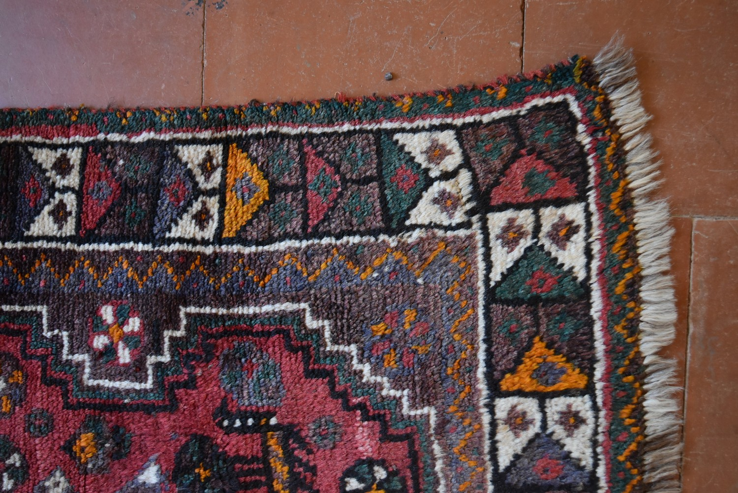 A Persian Shiraz rug with triple stepped pole medallion on burgundy field with stylised animal and - Image 3 of 4