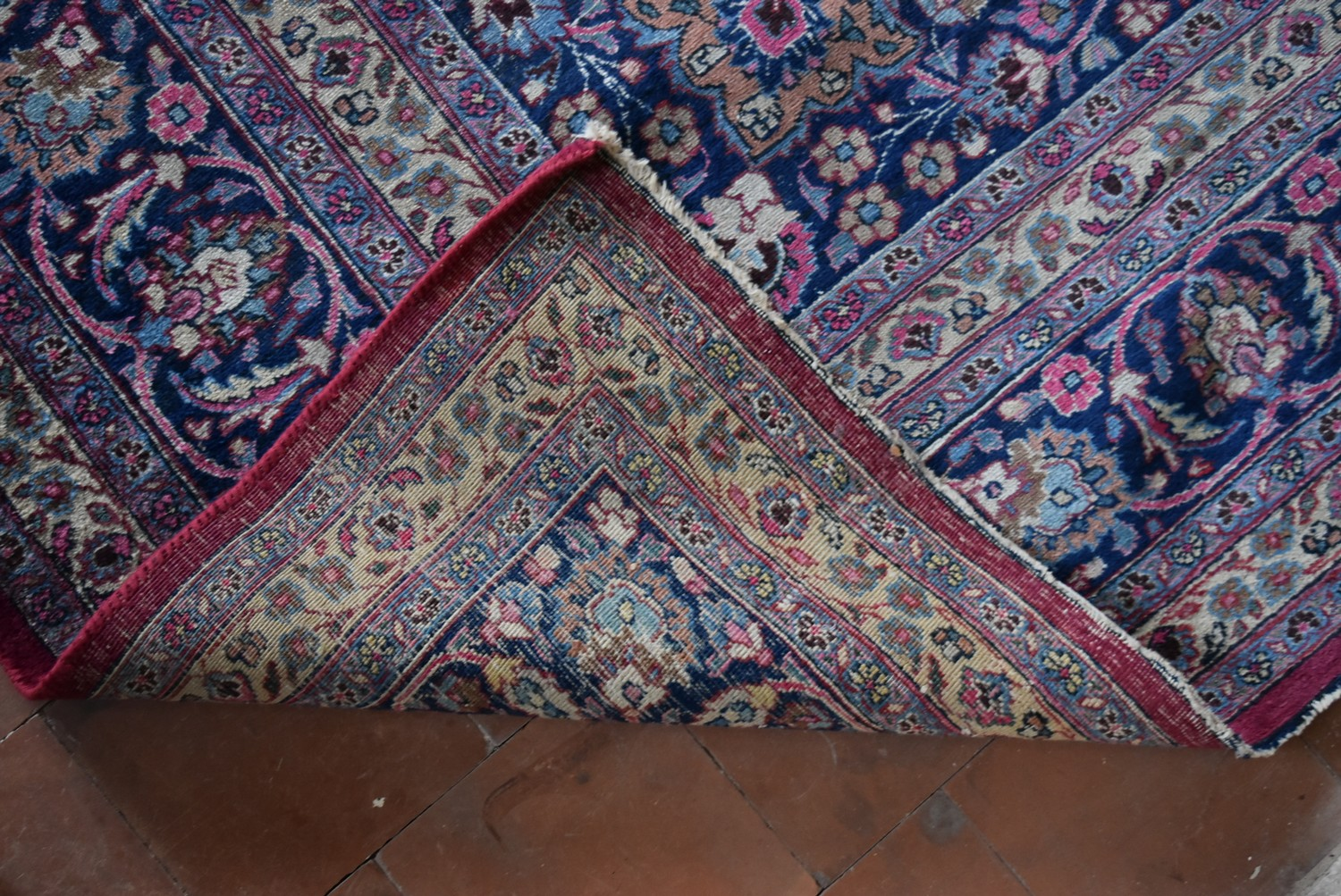 A Persian Mashad carpet with double central floral medallions on madder field within sapphire floral - Image 4 of 4