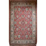 A Persian style flat weave carpet with scrolling leaves on madder ground within floral borders. L.
