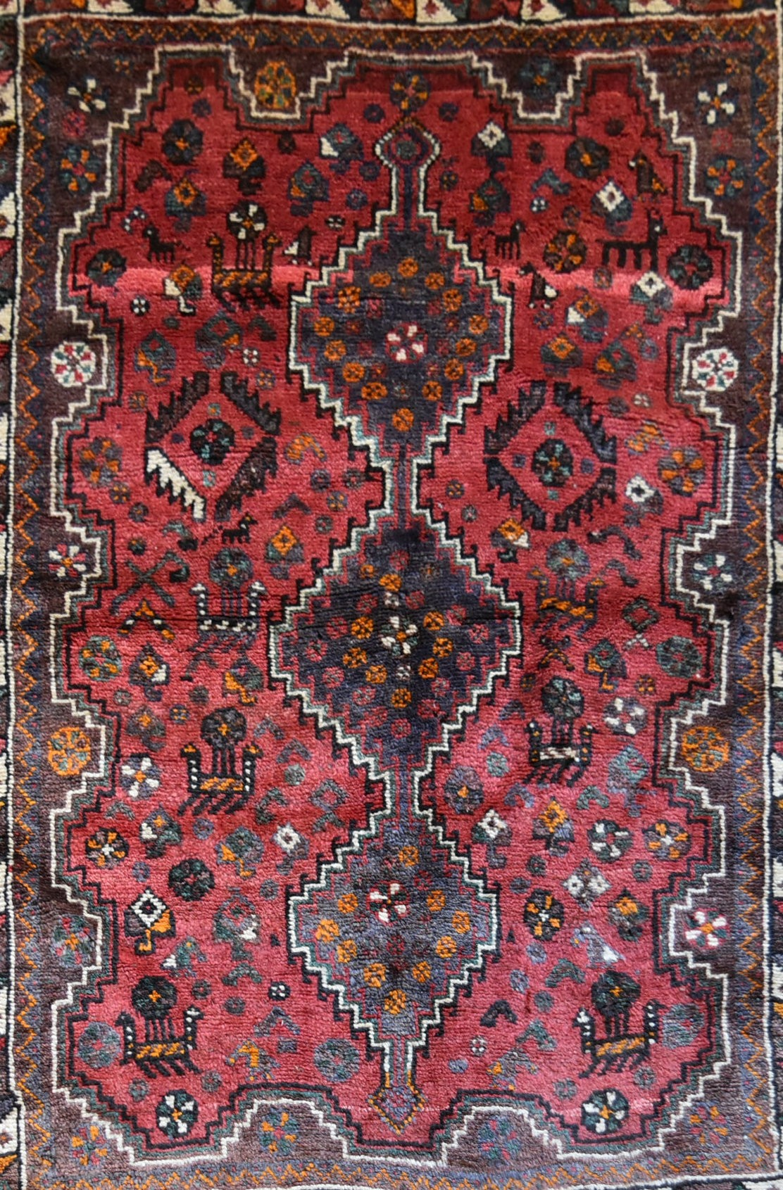 A Persian Shiraz rug with triple stepped pole medallion on burgundy field with stylised animal and - Image 2 of 4