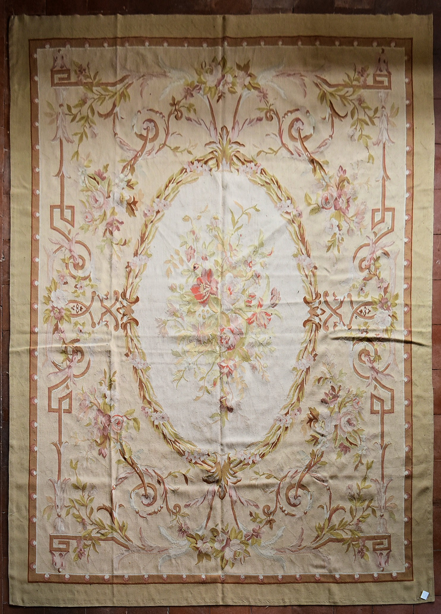 A hand made Aubusson carpet with central oval medallion with floral bouquet on a scrolling foliate
