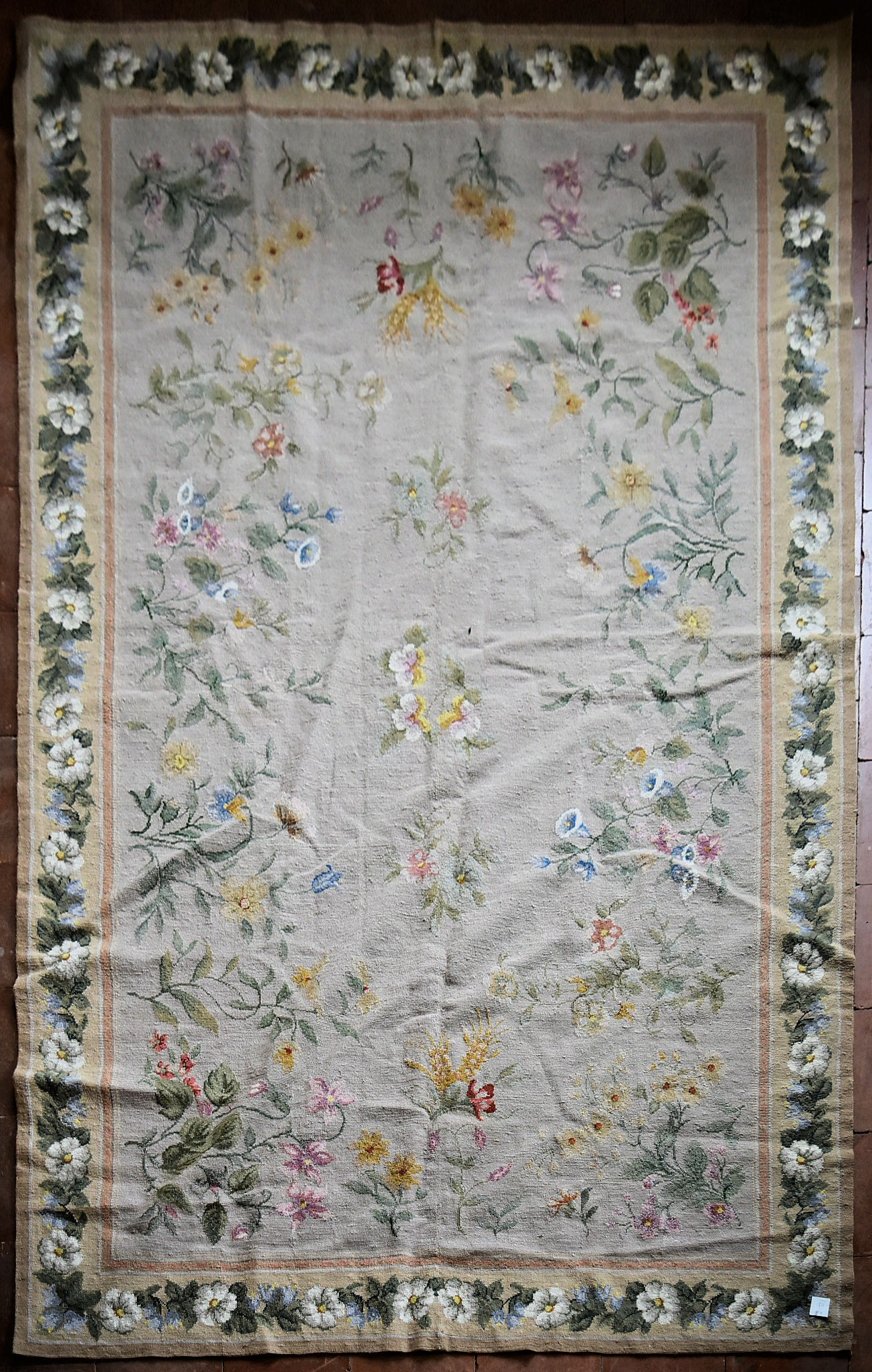 A needlepoint rug with foliate and wild flower sprays across a fawn field contained by garlands of