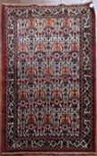 A Persian Hamadan rug with all over herati design on fawn ground within floral borders. L.100xW.