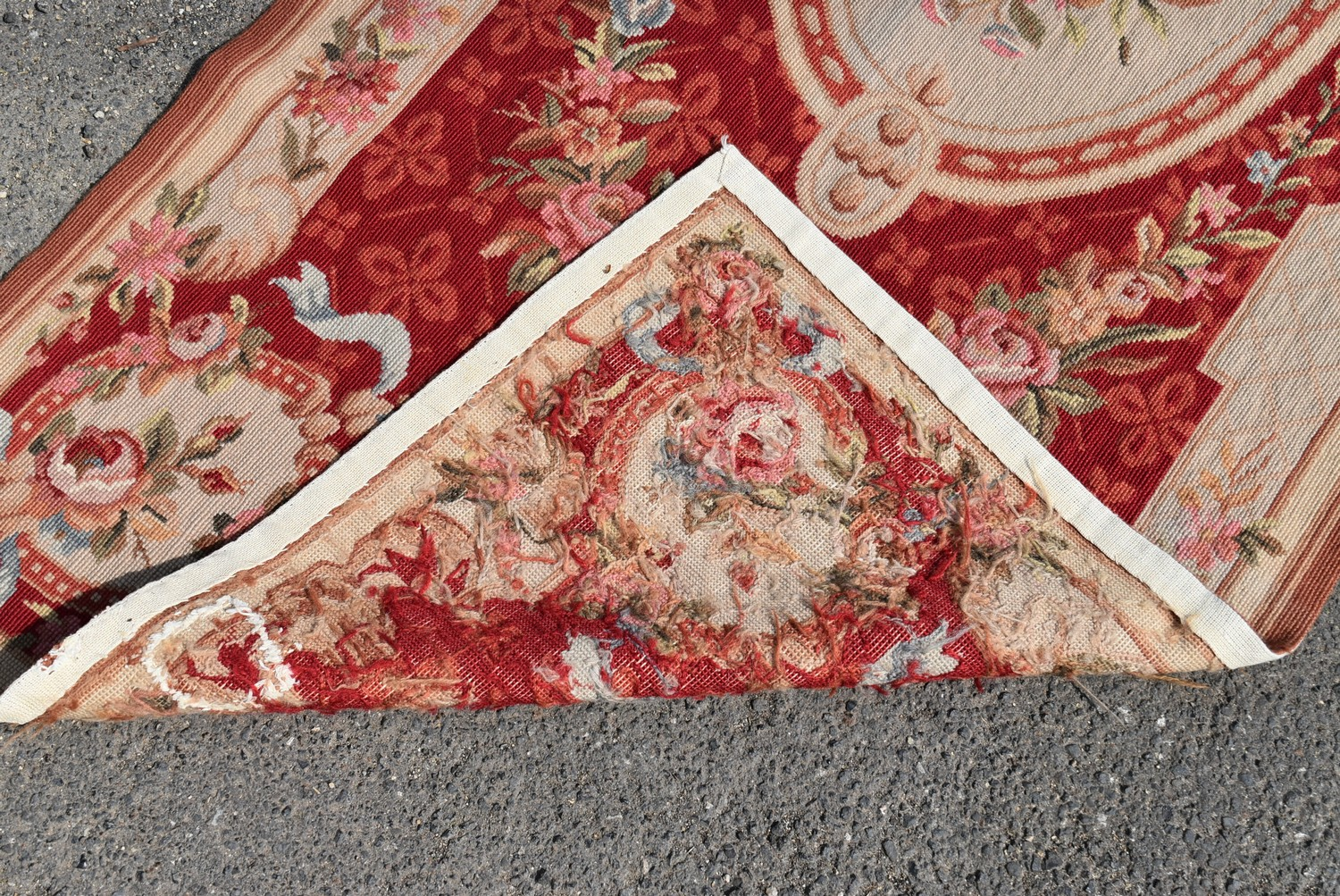 A needlepoint rug with central floral cartouche on a burgundy field within ribbon and flowerhead - Image 4 of 4