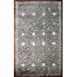 A Moroccan style rug with stylised motifs within repeating diamond panels across the field contained