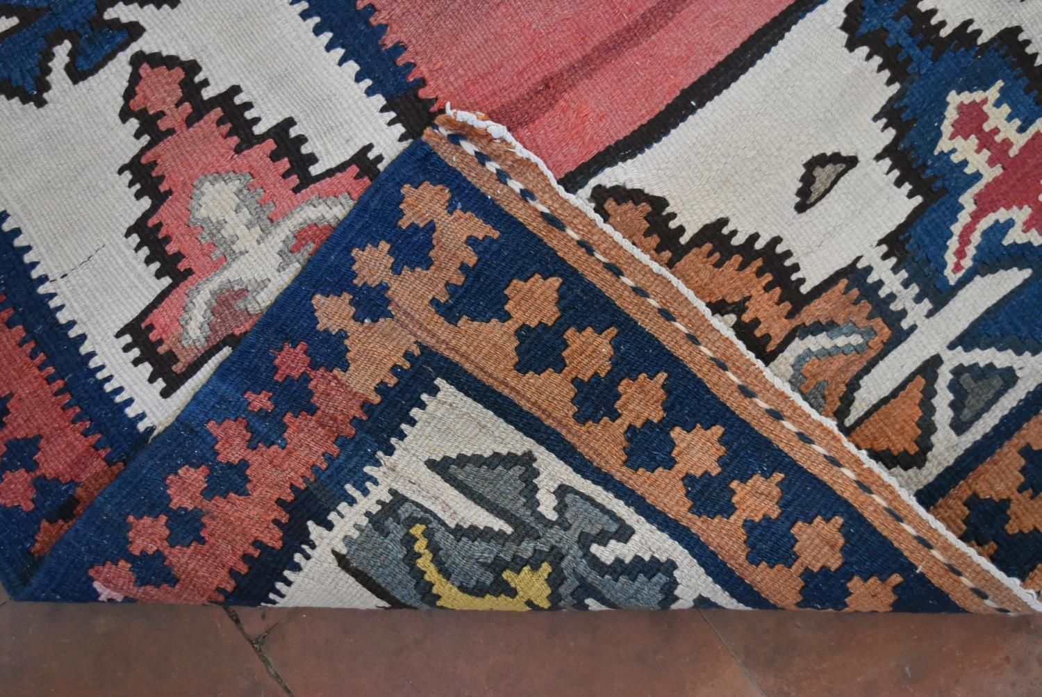 A Persian Kilim with repeating lozenge medallion on umber ground contained by plain spandrels and - Image 4 of 4