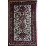 A Turkish Rug with repeating central medallions on ivory ground within stylised floral multi