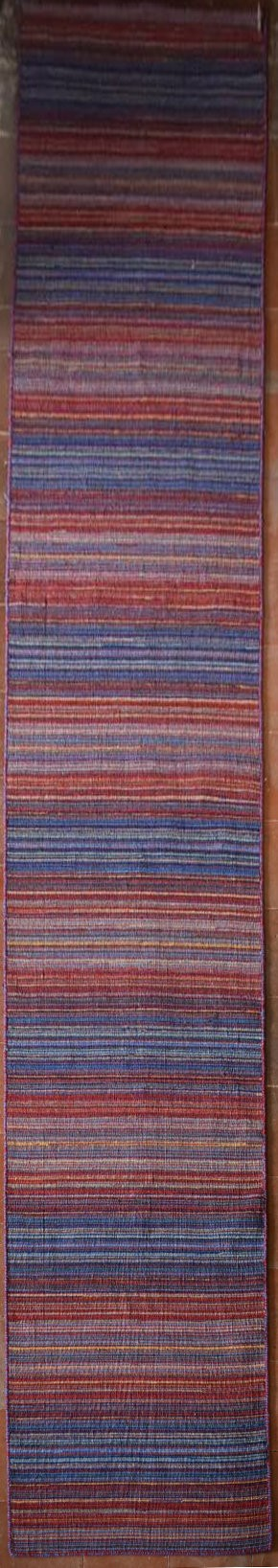 A long modern Kilim runner with bands in various hues of red and blue. L.400xW.70cm