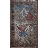 An antique Persian pictorial rug with animals and foliage in a mountain setting within stylised