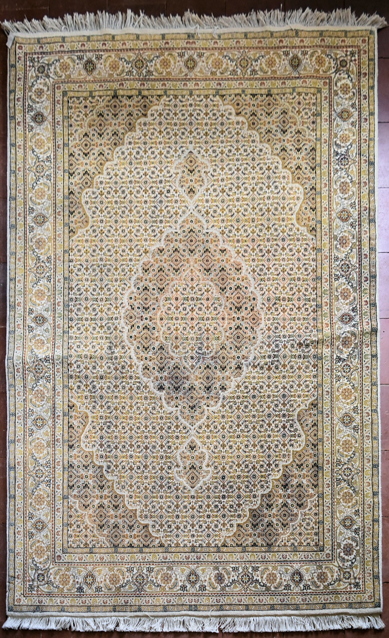 A silk & wool Tabriz style carpet with central medallion and repeating floral design across the fawn