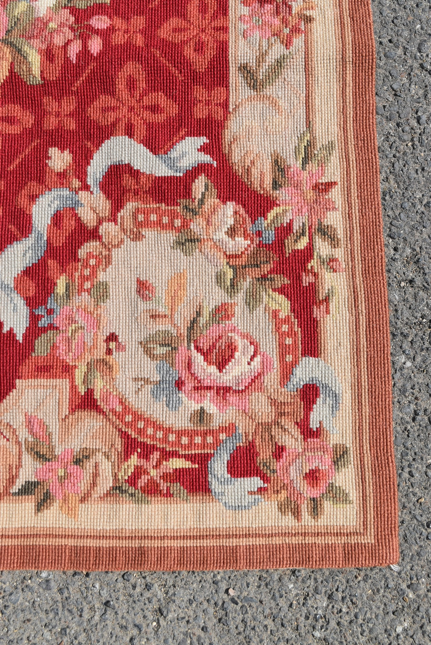 A needlepoint rug with central floral cartouche on a burgundy field within ribbon and flowerhead - Image 3 of 4