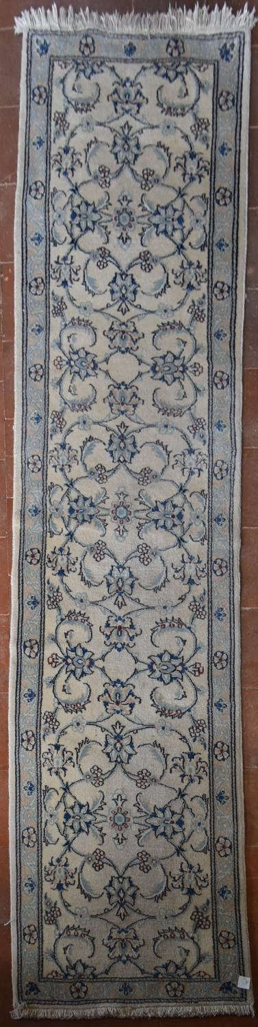 A Persian silk and wool Naiin runner with scrolling leaf and lotus pattern on the fawn ground within