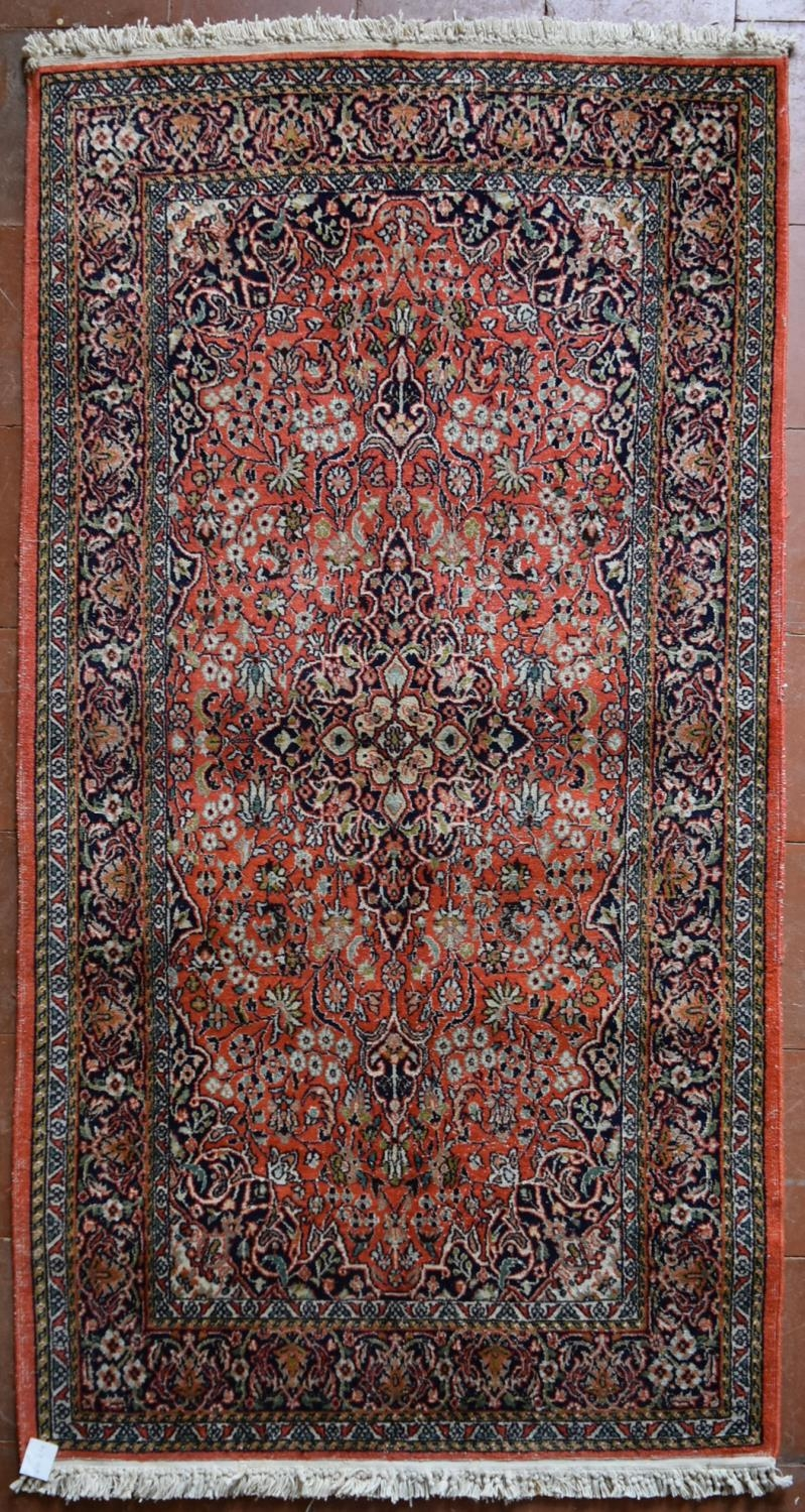 A silk Kashmir rug with central pendant medallion on madder field contained within floral