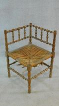 A 19th century mahogany corner chair with well turned spindles, legs and stretchers with rush