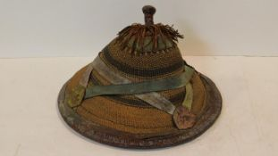 An African Fulani hat of conical form from woven fibres and leather. D.40cm