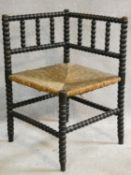 A late 19th century ebonised bobbin turned corner chair with woven rush seat on stretchered