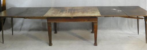 An early 20th century oak extending dining table with central leaf fitted to the underside and