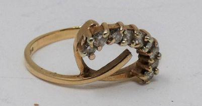 A 9ct yellow gold and diamond stylised floral design ring. Set with eight round brilliant cut
