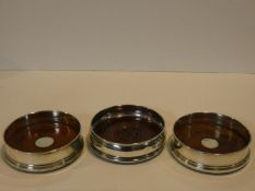 Three silver and oak wine coasters. Hallmarked: B&co for W I Broadway & Co. Two with central