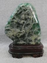 A large polished Fluorite crystal boulder mounted on a carved Chinese wooden stand. H.31cm