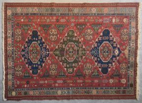 A Sumak Kilim with repeating pendant medallions on maroon ground surrounded by stylised floral and