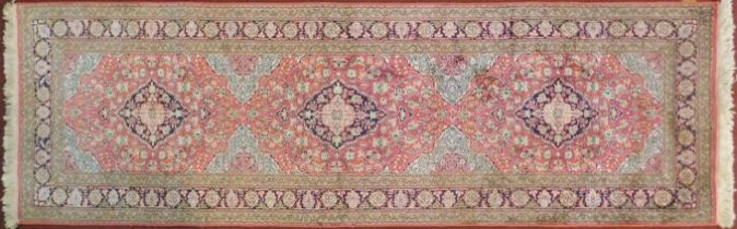 A Persian part silk runner with repeating triple medallions and scrolling floral decoration on a