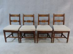 A set of four early 19th century mahogany dining chairs with carved backs and panel seats, fitted
