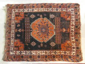 A Shirvan rug with central burgundy pole medallion on a midnight ground within stylised floral