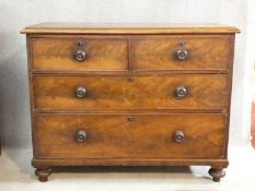 A 19th century mahogany chest of two short over three long drawers with knob handles on turned feet.