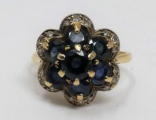 A vintage sapphire and diamond floral design 18ct yellow gold cluster ring. Set with seven round