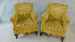 A pair of Georgian style armchairs in gold cut floral upholstery on walnut carved cabriole supports.