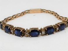 A vintage 9 ct yellow gold, sapphire and diamond articulated line bracelet. Set with seven oval