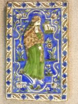 An antique Qajar Persian hand painted and polychrome glazed ceramic tile depicting a man in