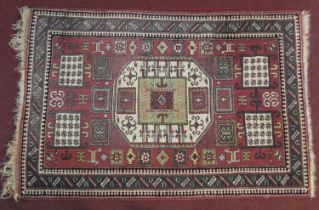 A Turkmenistan rug with central lozenge medallion on burgundy ground within geometric stylised