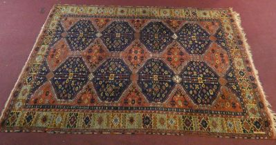 A Ushak carpet with repeating midnight lozenge medallions on a burgundy ground within geometric