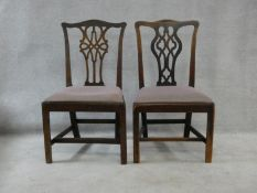 A near pair of Georgian mahogany dining chairs with pierced back splats and drop in seats on